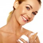 Beautiful woman applying body cream — Stock Photo