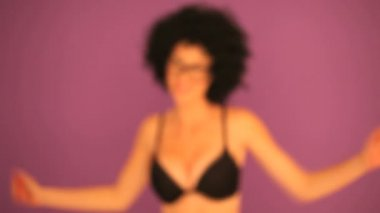 Woman with a large curly black afro hairstyle and glasses stepping into focus against a purple background