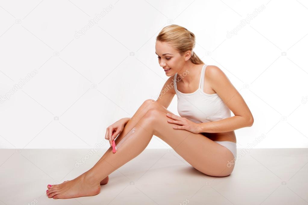 Beautiful woman removing her leg hair - Stock Image