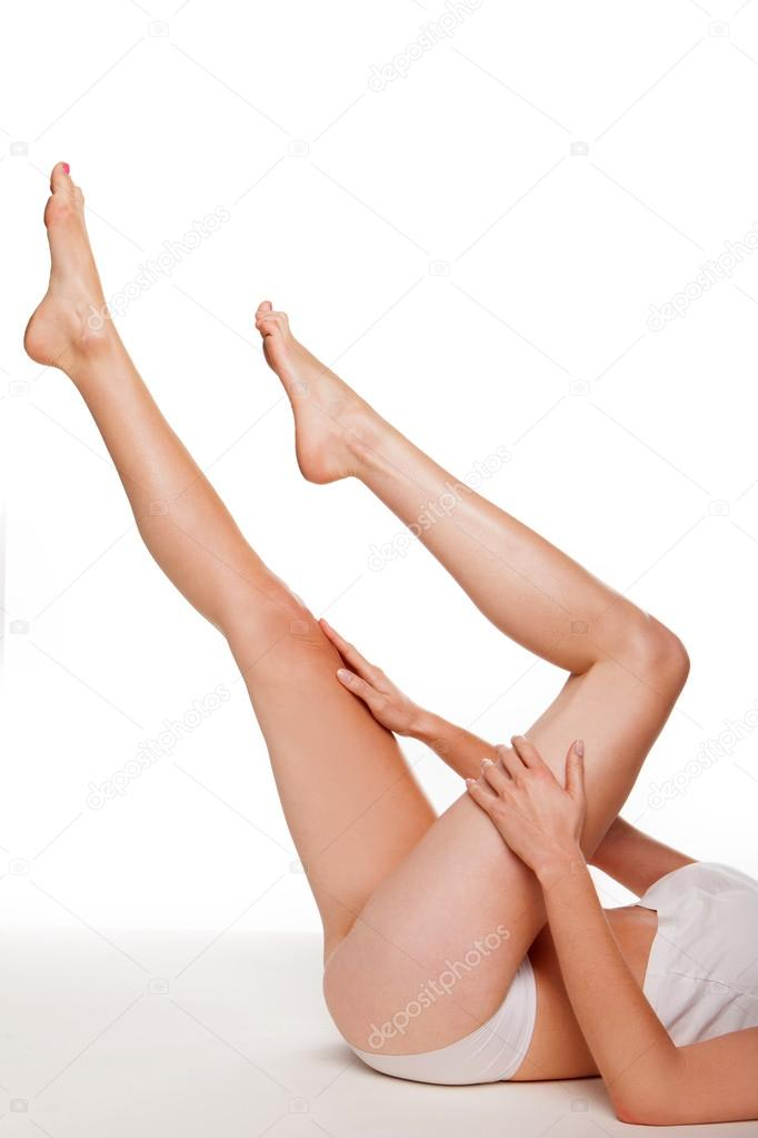 Sexy bare female legs in graceful pose pointing up into the air as the woman lies on her back doing yoga exercises in a health and beauty concept — Stock Photo #13820935
