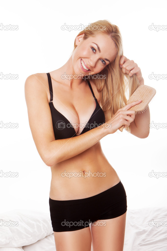 Blonde woman wearing black lingerie brushing her hair after wake up  standing close  to bed. blonde woman wearing black lingerie brushing her hair after wake up  sta  Stock Photo #13855523