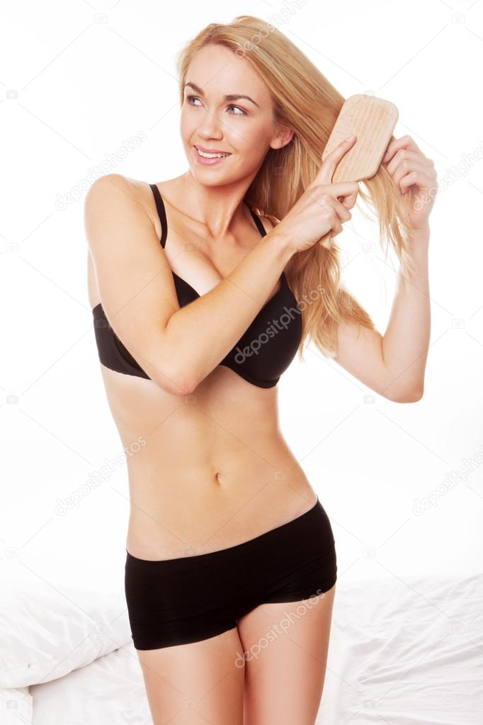 Blonde woman wearing black lingerie brushing her hair after wake up  standing close  to bed. blonde woman wearing black lingerie brushing her hair after wake up  sta — Stock Photo #13855526