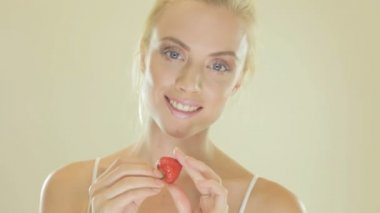 Attractive blonde woman eating a strawberry — Stock Video