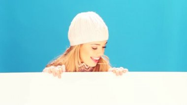 Smiling blonde woman dressed in winter woolies holds a large blank white sign.