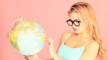 Laughing blonde woman in oversized glasses playing with a world globe, concept spoof for a studious person.