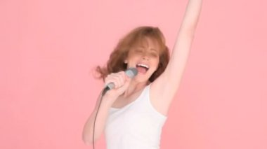 Close-up image of the face of a female singer with her mouth open in song holding a microscope.