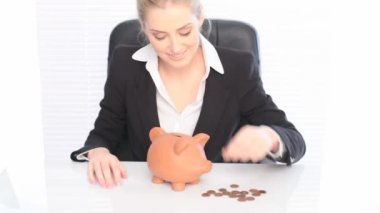 Business Piggy Bank Savings, a smiling businesswoman sits at her desk placing coins in a piggy bank, savings concept