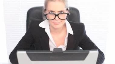 Fun Portrait Woman Wearing Huge Glasses, a businesswoman sits at her laptop wearing huge black framed glasses in a humorous portrait