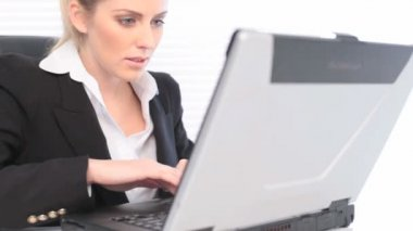 Businesswoman Working On Laptop with look of concentration, close up with copyspace.