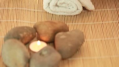 Spa Stones And Candle arranged on a reed mat.
