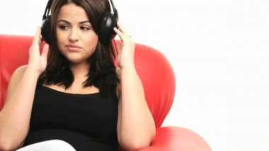 Young woman with headphones sitting listening to music on the sofa, closeup