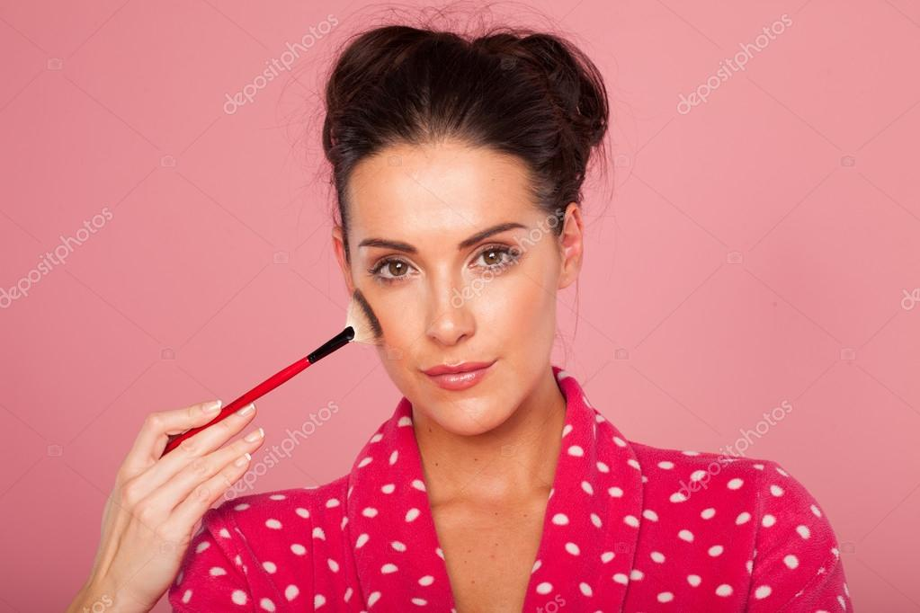 Glamorous woman applying blusher with a large soft bristle cosmetics brush to contour her cheekbones — Stock Photo #14210923