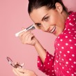Beautiful woman applying foundation - Stock Photo