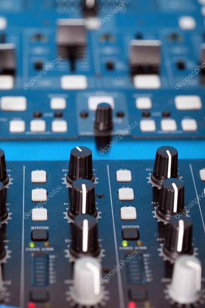 Control knobs on the console of a DJ deck for mixing, crossfading, equalising and volume of music for a disco, dance or nightclub — Stock Photo #14271573