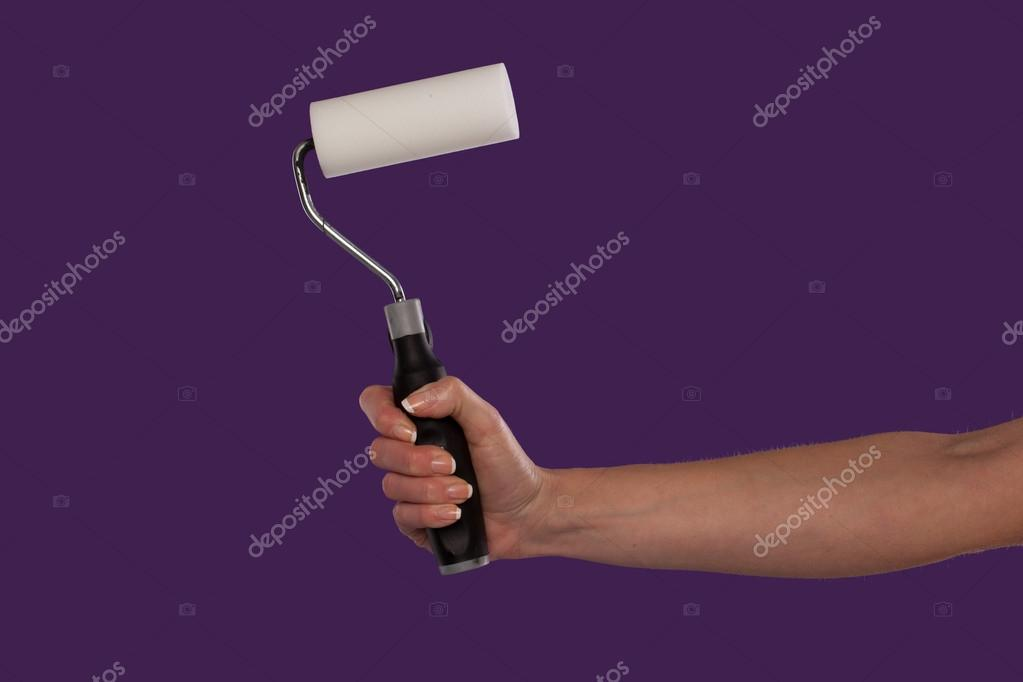 Female hand holding a paint roller over a purple studio background in a DIY and home redecorating concept — Stock Photo #14431167