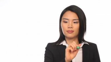 Attractive stylish young Asian businesswoman writing on a virtual screen interface with a pen against a white studio background