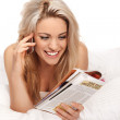 Woman chatting on her mobile on her bed — Stock Photo