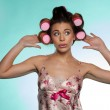 Vain pretty young woman showing her hair rollers — Stock Photo