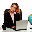 Businesswoman with a world globe on her desk — Stock Photo #26321733