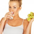 Woman drinking water and eating grapes — Stock Photo
