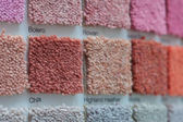 Carpet samples in shades of red, orange and pink — Stock Photo