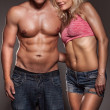 Stock Photo: Fitness image of a man and woman's torso isolated on black