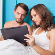 Young couple browsing internet on tablet computer while sitting in bed — Stock Photo