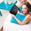 Couple with digital tablet lying on bed — Stock Photo #28655297