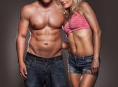 Fitness image of a man and woman's torso isolated on black — Stock Photo