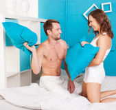 Young couple having fun making pillows fight. — Stock Photo