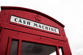 Red telephone booth converted to cash machine — Stock Photo