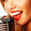Stock Photo: Beautiful womsinging into microphone