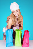Delighted woman peeking into her shopping bags — Stock Photo
