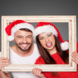 Couple looking through frame wearing Santa hats — Stock Photo