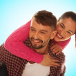 Playful young couple with woman riding piggyback — Stock Photo #33429161