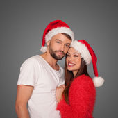 Loving couple wearing Santa hats — Stock Photo