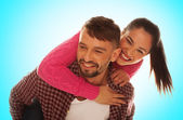 Playful young couple with woman riding piggyback — Stock Photo