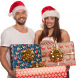Happy couple carrying Christmas gifts — Stock Photo