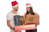 Smiling young couple with large Xmas gifts — Stock Photo