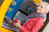 Beautiful smiling woman using an bank ATM — Stock Photo