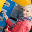 Stock Photo: Smiling wominserting her card in ATM