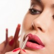 Young woman having lip gloss applied — Stockfoto