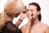 Beautician applying eye makeup — Stock Photo