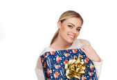 Woman holds a gift wrapped in christmas paper — Stock Photo