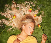 Seductive blond with her hair covered in roses — Stock Photo