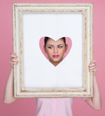Beautiful woman with her face framed by a heart — Stock Photo
