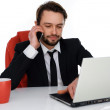 Businessman talking on his mobile at his desk — Stock Photo