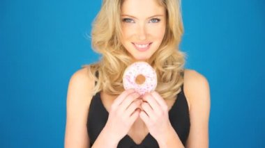 Beautiful blond woman eating a big doughnut — Stock Video