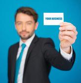 Pohledný podnikatel ukazující prázdná vizitka — Stock fotografie