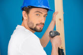 Builder using a drill looking at the camera — Стоковое фото